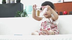 Menina asiática feliz que joga apenas no sofá em casa movimento 4K lento da criança fêmea bonita filme