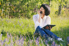 Menina asiática feliz que usa a tabuleta exterior Imagem de Stock
