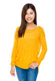 A menina asiática fresca de sorriso com mãos em suas calças de brim pocket Fotografia de Stock