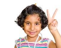 Menina asiática indiana feliz que sorri e que mostra o sinal da vitória imagem de stock