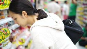 Menina asiática, mulher que anda, olhando e comprando no supermercado video estoque