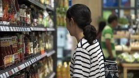 Menina asiática, mulher que anda, olhando e comprando o molho na ilha do supermercado video estoque