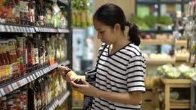 Menina asiática, mulher que anda, olhando e comprando o molho na ilha do supermercado filme