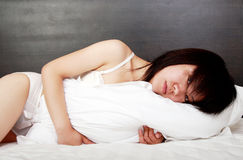 Menina asiática na cama. Fotos de Stock