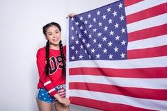 A menina asiática na camiseta com EUA exprime manter a bandeira americana isolada no cinza, o 4 de julho - Dia da Independência Imagens de Stock Royalty Free