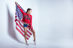 A menina asiática na camiseta vermelha com EUA exprime o levantamento com a bandeira americana isolada no cinza, o 4 de julho - D Foto de Stock
