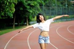 Menina asiática na pista de decolagem no campo de jogos da escola Foto de Stock