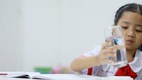 Menina asiática no fim uniforme da água potável do estudante tailandês do jardim de infância acima do tiro filme