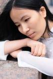 Menina asiática no perfil que coloca em suas mãos Fotos de Stock Royalty Free