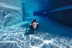 Menina asiática no roupa de banho, nadando sob a água foto de stock
