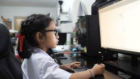Menina asiática no uniforme tailandês do estudante usando a tabuleta da pena à tiragem e à pintura digital com computador vídeos de arquivo