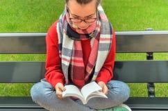 A menina asiática nos vidros lê um livro Foto de Stock Royalty Free