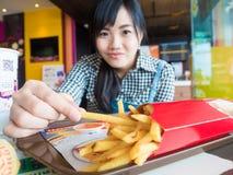 Menina asiática nova bonita que come batatas fritas fotografia de stock