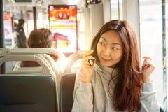 Menina asiática nova no ônibus que senta-se com um smartphone imagens de stock royalty free
