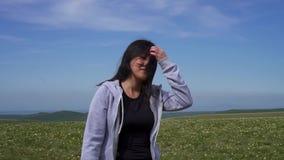 A menina asiática nova que anda em um campo ventoso nas montanhas e endireita seu cabelo vídeos de arquivo