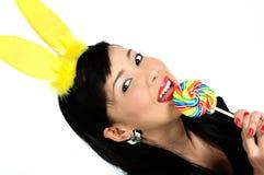 Menina asiática nova que come o lollipop Fotos de Stock