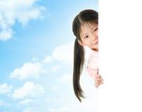 Menina asiática que esconde atrás de um cartão branco vazio Fotografia de Stock