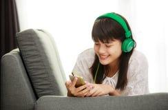 Menina asiática nova que escuta a música com fones de ouvido e smarthpho Fotografia de Stock Royalty Free