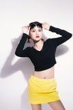 Menina asiática nova que faz a emoção Vestido em uma camisa preta e uma saia amarela, uns vidros e uns bordos brilhantes, roupa n fotos de stock