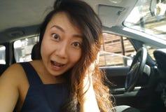 Menina asiática nova que senta-se para dentro de um carro e surpreendida olhando a câmera imagem de stock royalty free