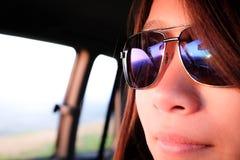 Menina asiática nova que veste óculos de sol azuis foto de stock