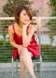 A menina asiática nova senta a vista ao ar livre a tomar o partido Imagens de Stock Royalty Free