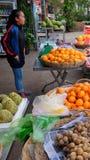 A menina asiática nova vende o fruto em uma rua da cidade imagens de stock royalty free