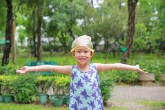 A menina asiática pequena adorável da criança que veste o tampão plástico na cabeça está feliz com a chuva fotos de stock