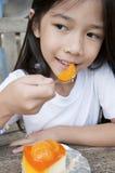 A menina asiática pequena aprecia a torta alaranjada do queijo. Imagem de Stock
