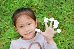 Menina asiática pequena bonito da criança que encontra-se no gramado da grama verde com etiquetas brancas vazias da exibição em s fotografia de stock