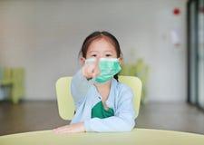 Menina asiática pequena bonito da criança que veste uma máscara protetora com apontar em você que senta-se na cadeira da criança  foto de stock royalty free