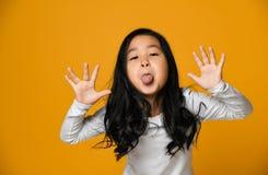 A menina asiática pequena bonito engraçada mostra a língua imagem de stock