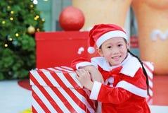 Menina asiática pequena bonito feliz da criança no traje de Santa com a caixa de presente perto da árvore e do fundo de Natal Eng foto de stock