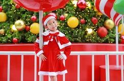 Menina asiática pequena bonito feliz da criança no traje de Santa perto da árvore e do fundo de Natal Conceito do feriado de inve imagens de stock