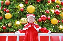 Menina asiática pequena bonito feliz da criança no traje de Santa perto da árvore e do fundo de Natal Conceito do feriado de inve foto de stock royalty free
