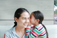 Menina asiática pequena bonito feliz da criança que sussurra um segredo a sua orelha nova das mães em casa Família e conceito dos fotografia de stock royalty free