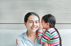 Menina asiática pequena bonito feliz da criança que sussurra um segredo a sua orelha nova das mães em casa Família e conceito dos imagem de stock