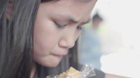 Menina asiática pequena bonito na roupa ocasional que senta-se para apreciar o livro de leitura no café video estoque