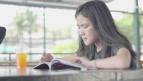 Menina asiática pequena bonito na roupa ocasional que senta-se para apreciar o livro de leitura no café filme