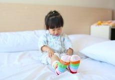 A menina asiática pequena bonito veste peúgas na cama foto de stock royalty free
