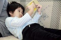 Menina asiática pequena com brinquedos. Imagem de Stock