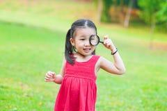 Menina asiática pequena com vidro da lente de aumento fotografia de stock