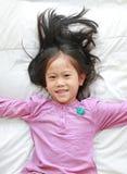Menina asiática pequena da criança do close-up que encontra-se na cama que olha a câmera Acima da vista imagem de stock royalty free