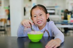 A menina asiática pequena de sorriso aprecia comer o gelado no copo que senta-se na tabela no café fotos de stock