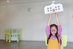 Menina asiática pequena de sorriso da criança nos brins cor-de-rosa-amarelos que guardam a escola do papel do modelo que senta-se imagens de stock