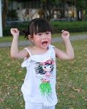 Menina asiática pequena do retrato que grita no parque exterior fotografia de stock