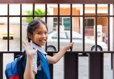 A menina asiática pequena em uniforme diz adeus antes de sair à escola na manhã com a trouxa azul fotografia de stock royalty free