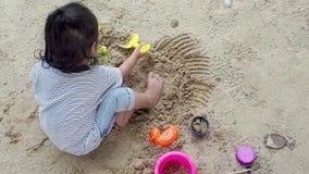A menina asiática pequena está jogando a areia no campo de jogos Jogar é um desenvolvimento de aprendizagem E músculo da construç filme