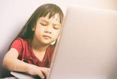 A menina asiática pequena está trabalhando seriamente em um laptop fotos de stock