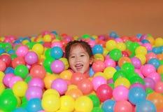 Menina asiática pequena feliz da criança que joga com o campo de jogos plástico colorido das bolas imagens de stock royalty free